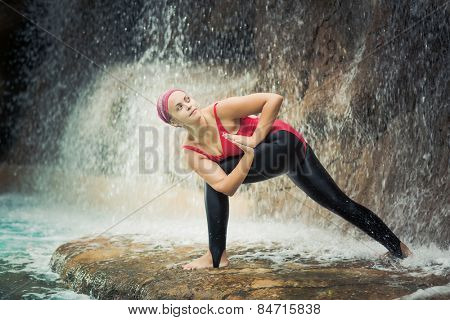Woman practicing yoga near waterfall. Revolved Side Angle. Parivrtta Parsvakonasana