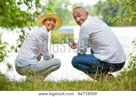 Senior people learning to paint in art class in nature on a lake