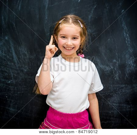 Cute little girl on a background of black school board raised a finger up her idea arose