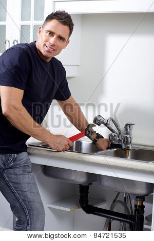Plumber man with tools in the kitchen. Plumbing and renovation.
