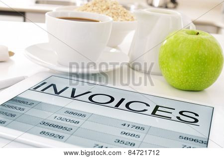 a tablet computer with a spreadsheet of invoices and a cup of coffee, a bowl with cereals and an apple on the kitchen table