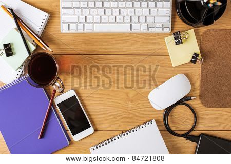 Office supplies, keyboard and coffee cup on wooden table