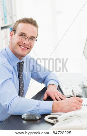 Smiling businessman with glasses taking notes in his office