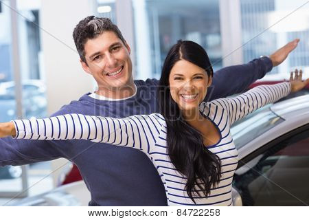 Happy couple standing with arms outstretched at new car showroom