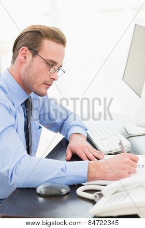 Businessman with glasses taking notes in his office