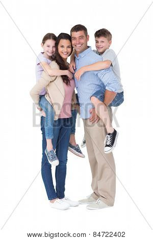 Full length portrait of parents giving piggyback ride to children over white background