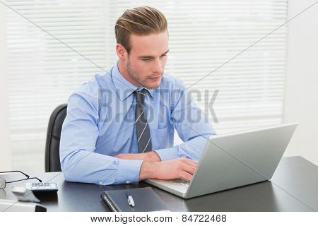 Concentrated businessman using his laptop in his office