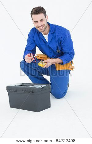 Portrait of happy repairman kneeling by toolbox against white background