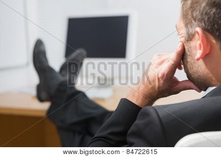 Relaxed businessman with his feet up in his office