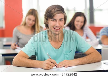 Portrait of male student writing notes in classroom