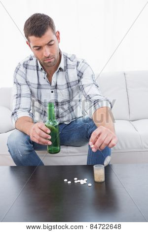 Preoccupied man with a beer and his medicine laid out on coffee table