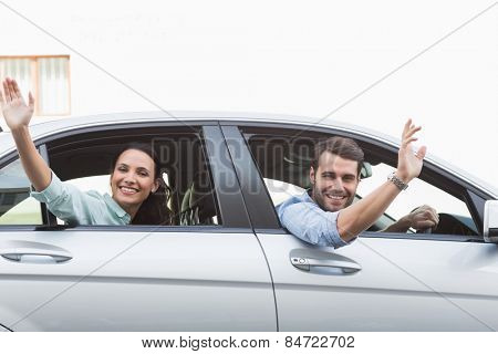 Young couple smiling and waving in their car