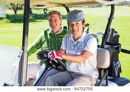 Golfing friends driving in their golf buggy smiling at camera at the golf course