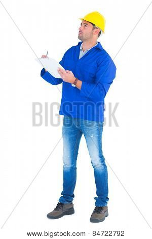 Full length of manual worker looking up while writing on clipboard over white background