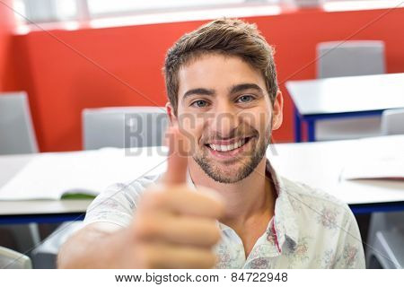 Portrait of smiling male student gesturing thumbs up in classroom