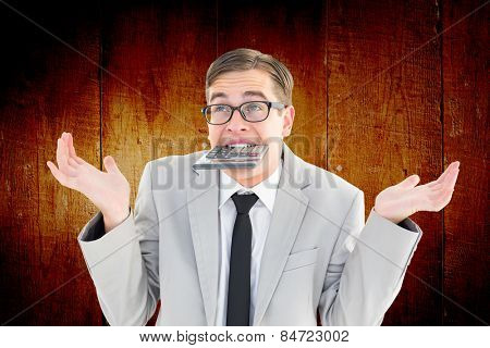 Geeky shrugging businessman biting calculator against wooden planks