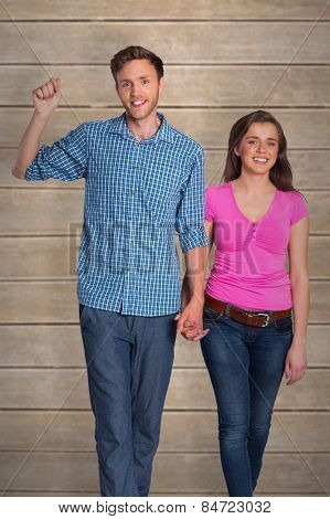 Full length of happy young couple against wooden planks