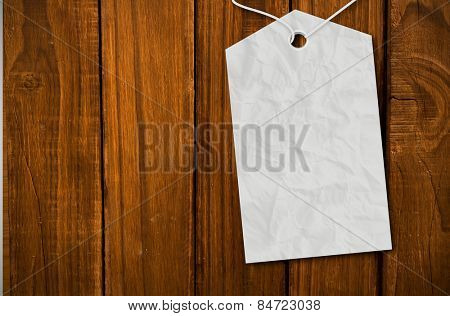 Crumpled paper tag against overhead of wooden planks