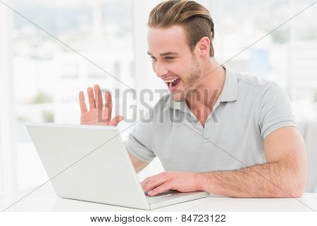 Happy businessman using laptop and gesturing in his office