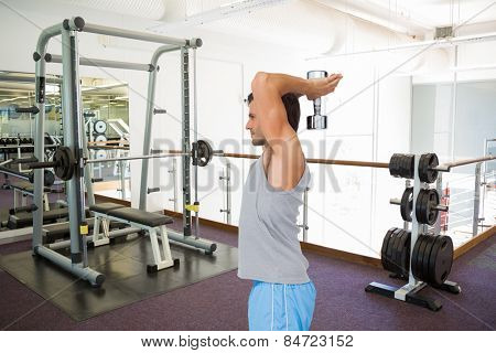 Side view of a fit man exercising with dumbbell against empty weights room with bench press