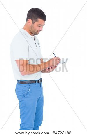 Side view of male supervisor writing on clipboard over white background