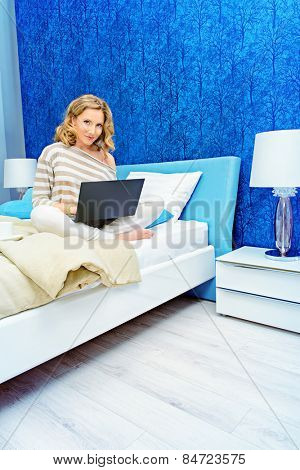 Smiling elegant woman sitting on a bed with her laptop computer in a bedroom. Home interior, furniture. Lifestyle.