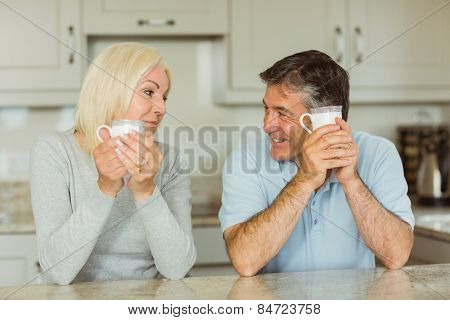 Happy mature couple having coffee together at home in the kitchen