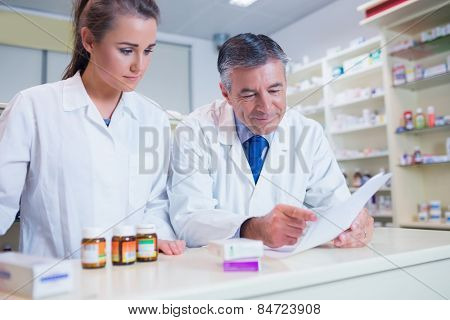 Pharmacist showing a prescription to his trainee in the pharmacy