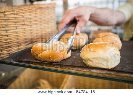 Hand of server taking bread with tongs at the bakery