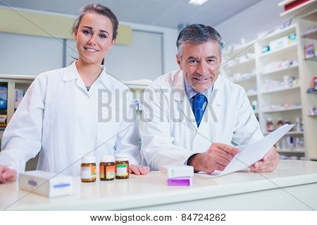 Pharmacist holding a prescription next to his trainee in the pharmacy