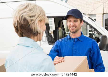 Delivery driver passing parcels to happy customer outside the warehouse