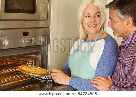 Woman taking fresh pie out of oven with husband at home in the kitchen