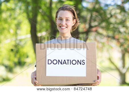 Happy volunteer in the park holding box on a sunny day