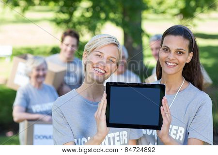 Happy volunteer friends showing tablet pc screen on a sunny day