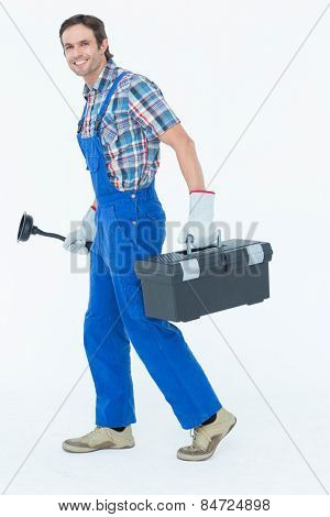 Full length portrait of plumber carrying plunger and tool box over white background