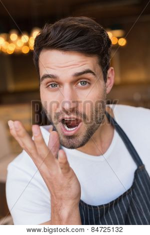 Handsome waiter making tasty gesture at the cafe