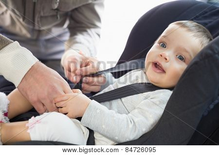 Parents securing baby in the car seat in his car