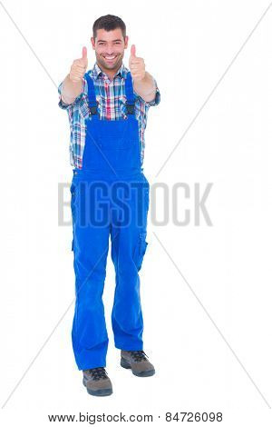 Full length portrait of happy handyman in coveralls gesturing thumbs up over white background