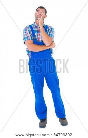 Full length of thoughtful handyman in coveralls looking up on white background