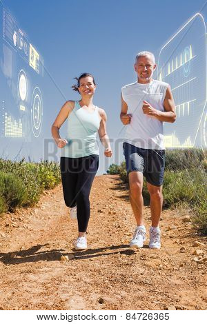 Fit couple running down mountain trail against fitness interface