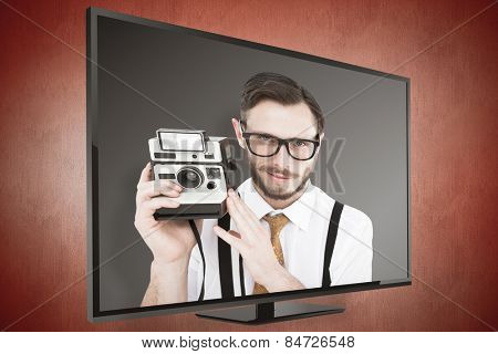 Geeky hipster holding a retro camera against orange