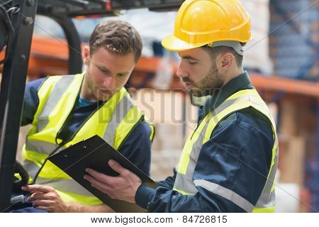 Focused warehouse workers talking together in warehouse