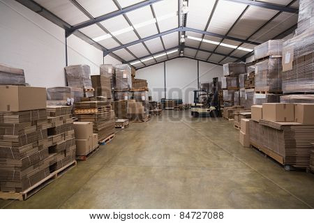 Forklift amid rows of boxes in a large warehouse