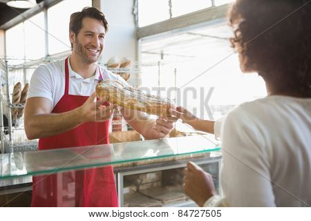 Smiling baker doing loaf transaction with customer at the bakery