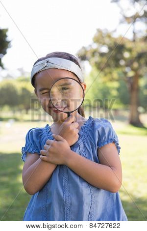 Curious little girl looking through magnifying glass on a sunny day