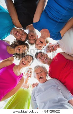 Low angle portrait of cheerful people forming huddle at gym