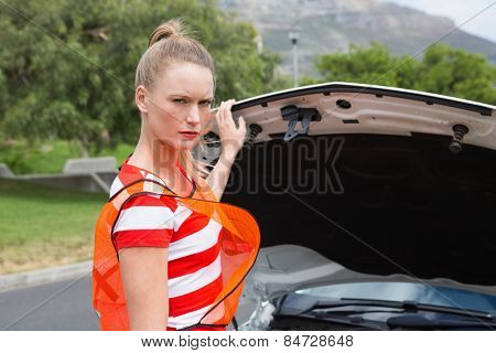 Worried young woman beside her broken down car in the street
