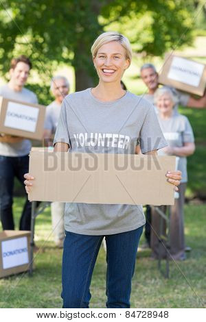 Happy volunteer blonde holding blank on a sunny day