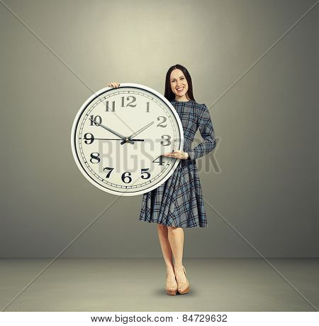 excited young woman holding big clock and pointing over dark background