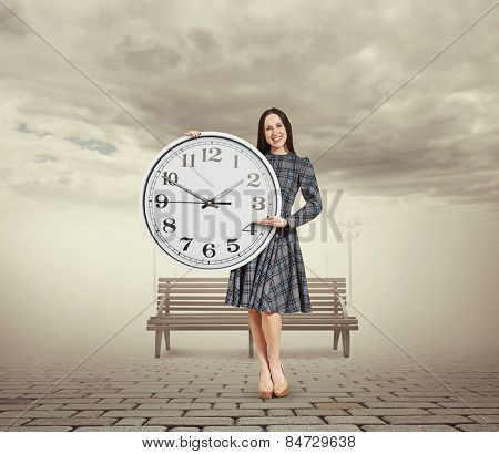smiley beautiful woman holding big clock and pointing at the time. photo in foggy park